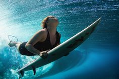 A surfer pierces a wave with her surfboard.
