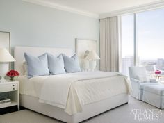 This restful white and light blue bedroom features a pale blue painted wall positioned behind a white upholstered bed dressed in white and ivory bedding topped with light blue pillows. Blue Master Bedroom, Blue Gray Bedroom, Blue Rooms, Light Blue Walls, Grey Walls, White Upholstered Bed, Discount Bedroom Furniture, Coastal Bedrooms, Trendy Bedroom