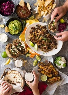 Overhead photo of Mexican Fiesta taco dinner party, with pork carnitas, tacos, grilled corn, guacamole, salsa, pickled red cabbage, tortilla chips and taco sides.