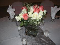 A coral and silver reception - white linens and chair covers with silver runners, coral chair sashes and coral and white rose centerpieces.