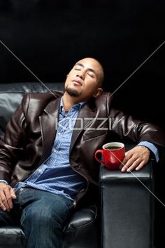 businessman relaxing on a couch with a cup of coffee. - Young African American businessman relaxing on a couch with a cup of coffee, Model: Eric Sychangco MUA: Thao Nguyen, Clothing Stylist: Tanya Rudolpho