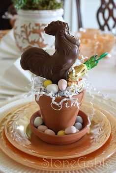 Such a cute DIY  place setting, small terra cotta pots and saucers, paper grass, edible candy eggs and chocolate (or any type of candy).  Name written on the pot.  Very cute Easter Tablescape idea