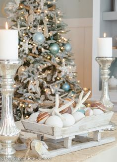Coastal Christmas Tree with rope as garland, distressed wooden sea ornaments, blue netting ornament balls and a burlap bow as a tree topper. Gorgeous sleigh filled with coastal ornaments and starfish as a centerpiece