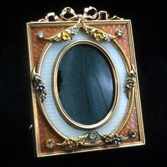 A Fabergé miniature picture frame with tangerine and white guilloché enamel embellished with applied quatre-color gold floral garlands and a gold bow surmount. Workmaster Johann Viktor Aarne, St Petersburg, circa 1900.