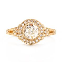 Incredible handcrafted details make this yellow gold engagement ring truly exquisite. Featuring an Old European cut center diamond bordered by a halo of sparkling round, brilliant diamonds, this unique ring is truly a one-of-a-kind find.  at Greenwich Jewelers