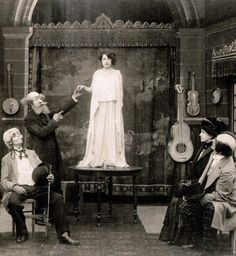 Georges Méliès (left, standing) as a medium in the lost film Phantom Apparitions (1910, dir. Georges Méliès)