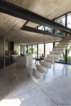 The main living area features a full glass frontage facing the mountains and stairs lead