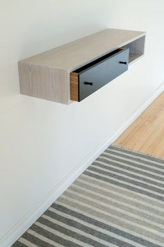 This floating hall table is handmade in solid white oak with a white wash finish, and an ebonized drawer front. Expertly crafted in my small shop,