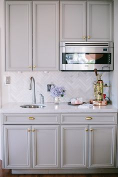 Style At Home: Jordana Hazel Herringbone marble backsplash, brass fixtures, love the cabinet shape and color.