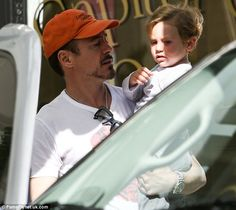 Daddy's boy: Robert Downey Jr. carried two-year-old son Exton in his arms as they left a restaurant following brunch over the weekend