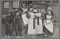 Een groep kinderen, jongens en meisjes, poseren in dracht. Enkele meisejes breien en een jongen heeft een hoepel. 1910-1920 #Urk