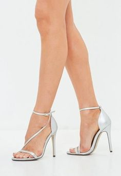 Silver heels featuring an asymmetric style, stiletto heel and ankle strap with adjustable fastening.