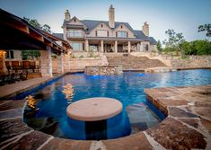 One-of-a-kind pool with swim up bar designed by Cascade Custom Pools!