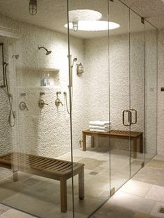 Amazing glass enclosed shower with stone walls.