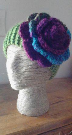 Ear warmer, knit in Oklahoma City Green yarn, with rose crocheted in Mulberry yarn, done by Jodi Villanella.