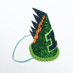 This is our Green Dinosaur Glitter Birthday Hat made in bold Green and Blue colours. A perfect First birthday hat and smash cake photo shoot prop. Please see our other listing if you want pastel colours. Dinosaur First Birthday, First Birthday Hats, Baby Boy 1st Birthday, Birthday Party Hats, Dinosaur Party, First Birthdays, 4th Birthday, Birthday Ideas, Baby First Cake