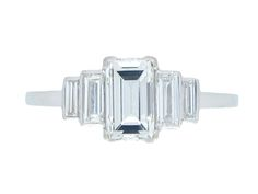 Art Deco baguette diamond ring. Set with a central rectangle baguette cut diamond in an open back corner claw setting with a weight of 1.50 carats, flanked by two tapered stepped rows of four rectangle baguette cut diamonds in open back rubover settings with a combined weight of 0.60 carats. The total approximate diamond weight is 2.10 carats, supported by an intricate pierced geometric open work gallery with rectangular backholing and slightly raised shoulders, flowing down to a square…