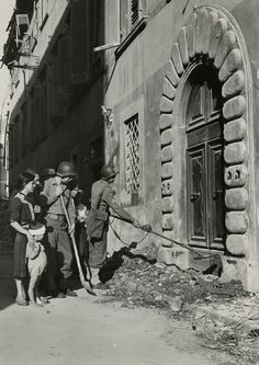 Safeguarding civilians in Pisa.-Special U.S. Army Police use a mine detector on debris in front of a doorway in Pisa, Italy, before allowing citizens to enter the premises. AFHQ, Sept. 16th, 1944.