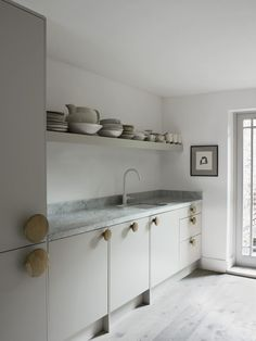 T WINTER TRAVEL - T Magazine Oversize wooden coat hooks are used as handles for the kitchen's Ikea cabinets.