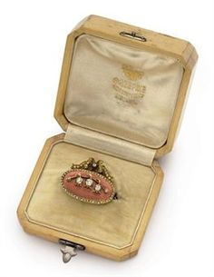 A Jewelled Gold-Mounted Guilloché Enamel Brooch By Fabergé, St Petersburg, circa 1898. Oval, enamelled in translucent pink over a hatched guilloché ground, applied with a diamond-set sprig of lily-of-the-valley within a diamond-set border surmounted by a diamond-set ribbon-tied bow, with gold chain. Given by Empress Alexandra Feodorovna to Marion Louisa 'Pollie' Delmé-Radcliffe, Baroness Ungern-Sternberg, June 1898.