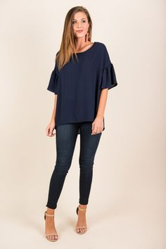 If you are wanting to have an adorable, versatile top that you can wear with many different bottoms, then look no further! This top can successfully be paired with skinnies or tucked into a skirt and jewelry is a breeze! So many colors look great with navy! Those ruffled sleeves are precious too! Material has no amount of stretch. Chelsea is wearing the small.