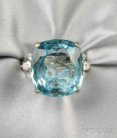 18kt White Gold, Aquamarine, and Diamond Ring, set with a cushion-cut aquamarine measuring approx. 18.70 x 17.10 x 9.80 mm, flanked by pear- and baguette-cut diamonds