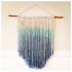 This macramé wallhanging was hand-dyed. It fades from off-white (with dark specks) into a turquoise into a light denim blue (coloring may vary slightly