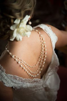 Love this pearl necklace draped down the bride's back and her pearl earring ~ we ❤ this! moncheribridals.com