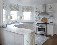 gray   white kitchen, white cabinets, marble countertops, stainless range   hood.Roman shades in the kitchen.
