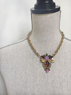 """This one of a kind necklace was created using a variety of repurposed vintage materials. The pendant is made up of three vintage earrings, various other rhinestones, and a lilac resin flower. They have been adhered to a natural goat leather back using and industrial strength adhesive, and attached to a vintage gold toned chain. Colors include: amber, olive green, amethyst, lilac, and a deep ruby red (which is only visible as red if the light hits it right.) Length: 17.5"""" (can add adjustable…"""