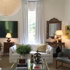 Compared to Michel Boyd's dark and dramatic study, @shaunsmithstyle's living room feels light and airy with its white silk drapery, white sofa and white walls. However, this room is anything but boring thanks to green and yellow accents, gorgeous antique pieces, an oversized modern light fixture and a white lacquered ceiling. From Arianne Bellizaire, www.inspiredtostyle.com