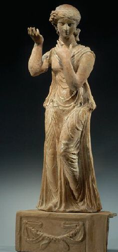 LARGE HELLENISTIC TERRACOTTA DRAPED FEMALE dressed in a chiton. With her upraised arms she plaits a braid from which single strands remain on the inside of her left hand. On the right side of her head are attached numerous single locks. It now stands on a separately made square terracotta podium. Ca. 1st Century BC. Terracota, Ancient Beauty, Ancient Art, Greek Artifacts, Greek Antiquity, Mythological Characters, Classical Greece, Human Sculpture, Greek Culture