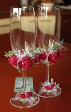 Beautiful wine glasses embellished with red roses & a touch of white tulle