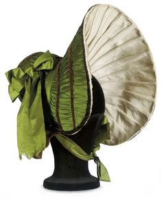 Bonnet: ca. 1830's, silk in an extravagant shape, wide-brimmed and lined in pleated silk, trimmed with velvet ribbons and wide silk ribbons.
