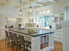 kitchens - coffered ceiling clear glass pendants white kitchen cabinets marble countertops white kitchen island beveled butcher block countertop brown leather modern counter stools white blue glass mosaic tiles backsplash