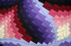 A closer view of Light in the Valley reveals the colors, sizes of the different squares, and the intricate quilting involved