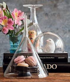 Taças, bowls e até aquele funil de vidro, usado em laboratórios, podem ganhar a função de redoma. Além de proteger quitutes e objetos delicados do pó e de insetos, o recurso dá destaque e uma aura especial para peças pequeninas, que poderiam passar despercebidas na decoração