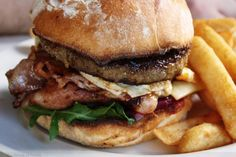 Juicy Hamburger on Sourdough with Fried Egg, Bacon, Cheese, Arugula, Beet and Sauteed Onions