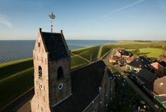 Aerial image of the old church of Wierum (well below sea level), with the North Sea in the background.