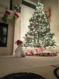 A BABY'S JOY AT CHRISTMAS IS MEASURED BY THE SIZE OF A TREE. HE IS TOO MESMERIZED BY ALL THAT HE SEES
