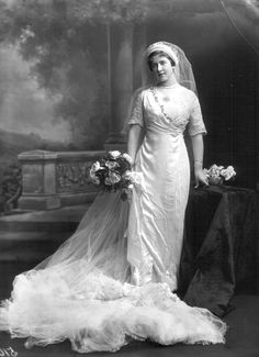 Katherine Stobart married Sir Reginald Guy Graham on the 18th of July 1911She wore a typically Edwardian structured gown of white satin with lovely Honiton lace sleeves and a train of white chiffon and satin. Her long tulle veil was topped by a crown of bay leaves and orange-blossom, and Katherine carried a bouquet of Frau Karl Droski roses, which was a gift from her groom.