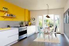 Bold pops of yellow colour and light flooding in - we love this kitchen! We can help design yours - visit www.designer.duluxamazingspace.co.uk