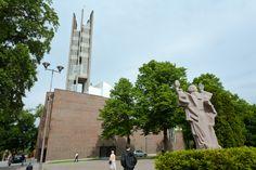 """Igreja da Cruz, em Lahti, província de Hämeen, Finlândia. Projetada por Alvar Aalto. A estátua """"Espírito da Liberdade"""", de Wäinö Aaltonen em frente.  Fotografia: Addison Godel no Flickr."""