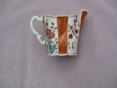 "A  Worcester ""high Chelsea ewer""  creamer finely painted in the Kakiemon manner  in the ""Scarlet Japan""  pattern with orange and gilt panels dividing panels of floral painting. Unmarked  Circa  1765 Height 3 1/2"""