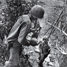 In a photo that somehow comprises both tenderness and horror, an American Marine cradles a near-dead infant pulled from under a rock while troops cleared Japanese fighters and civilians from caves on Saipan in the summer of 1944. The child was the only person found alive among hundreds of corpses in one cave. (W. Eugene Smith—Time & Life Pictures/Getty Images) See more: http://ti.me/Ot3lla