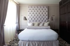 Gorgeous bedroom features a tall lilac tufted headboard lining lilac walls dressed in lilac and gold bedding as well as a lilac bolster pillow and a matching lilac bedskirt flanked by round bedside tables topped with arched table lamps accented with lilac pleated lamp shades atop a black and white zebra rug.