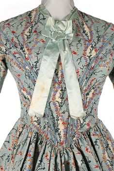 A printed wool day dress, late 1840s. with floral print on pale blue ground, braid outlining the V-shaped pleats to the waist, two tiered frills to skirt, bust 81cm, 26in, waist 66cm, 26in.