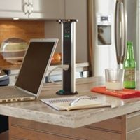 Laptop being charged on kitchen island with pop-up Sensio PowerPod