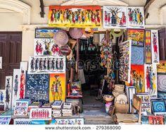 STONE TOWN, ZANZIBAR - MAY 02, 2015: Local store selling colorful tingatinga (tinga tinga) paintings with Maasai portraits and animals motives as souvenirs in Stone Town, Zanzibar, Tanzania, Africa. - stock photo