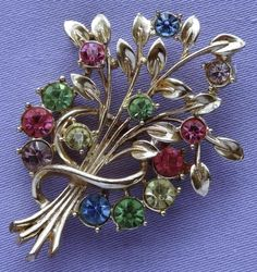 This fabulous, quality brooch has a lovely flower & leaf spray design. Made from pierced metal with a goldtone finish, it is adorned with shimmering multi-coloured faceted glass stones.